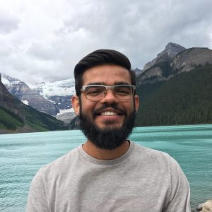 Man smiling in front of a lake in the mountains